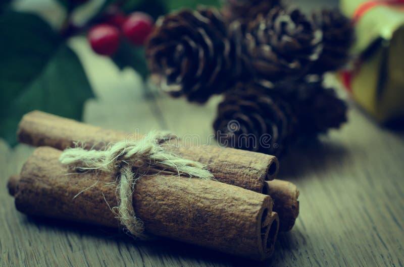 Paquete de los palillos de canela, acebo y conos de abeto en la tabla de roble - retra fotos de archivo libres de regalías