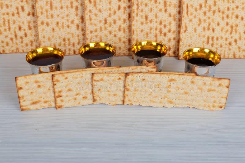 Paquete de matzah o de matza, Haggadah de la pascua judía y vino rojo kosher en un fondo de madera del vintage foto de archivo libre de regalías