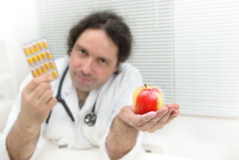 ¿Paquete de píldoras o de una manzana fresca al día? fotografía de archivo