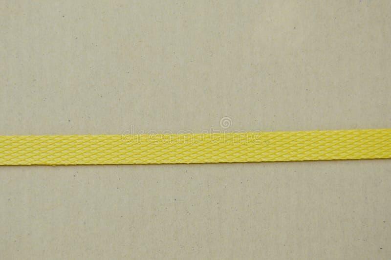Paquete de papel duro de Brown envuelto por la banda plástica amarilla imagen de archivo libre de regalías