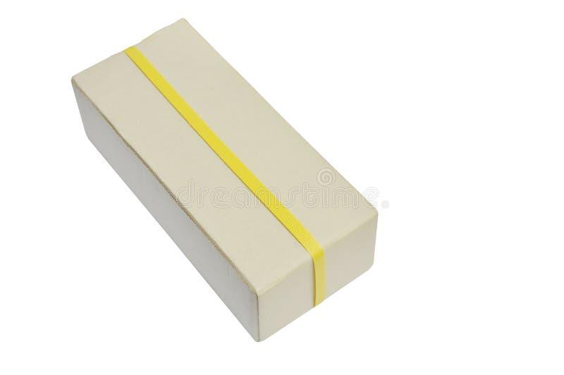Paquete de papel duro de Brown envuelto por la banda plástica amarilla en el fondo blanco imágenes de archivo libres de regalías