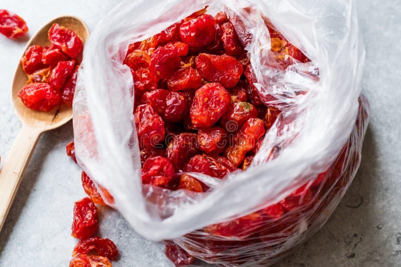 Paquete de pasas rojas en la bolsa de plástico con la cuchara de madera fotos de archivo libres de regalías