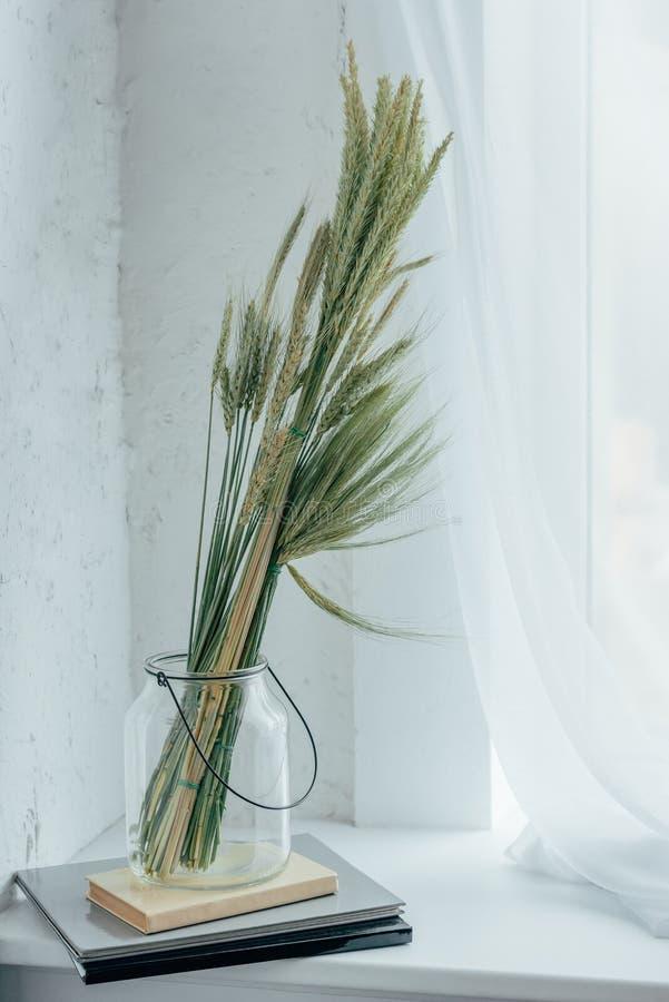 paquete de trigo secado en el tarro de cristal en los cuadernos imagenes de archivo
