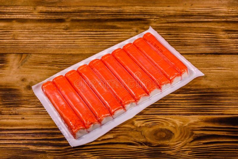 Paquete de vacío de palillos del cangrejo en una tabla de madera foto de archivo libre de regalías