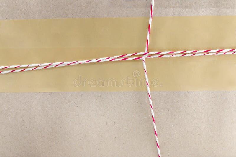 Paquete del paquete del correo de Brown con la cuerda roja y blanca imagen de archivo