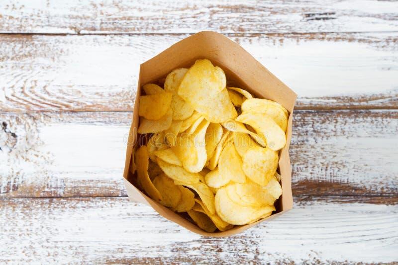Paquete en la tabla de madera vieja, concepto vegetariano del papel de patatas fritas fotografía de archivo libre de regalías