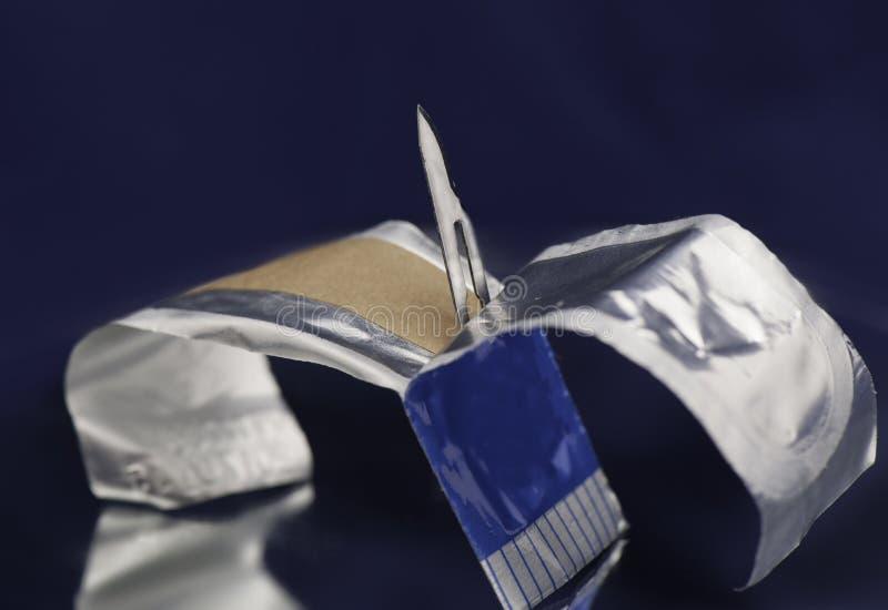 Paquete estéril abierto que contiene la cuchilla quirúrgica del escalpelo imagen de archivo