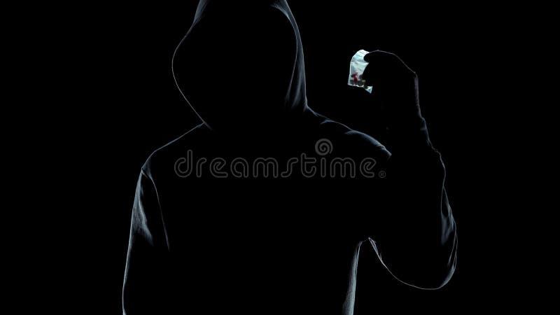Paquete masculino con las píldoras, crimen de los tráficos de droga, forma de vida de la tenencia de la silueta imagen de archivo libre de regalías