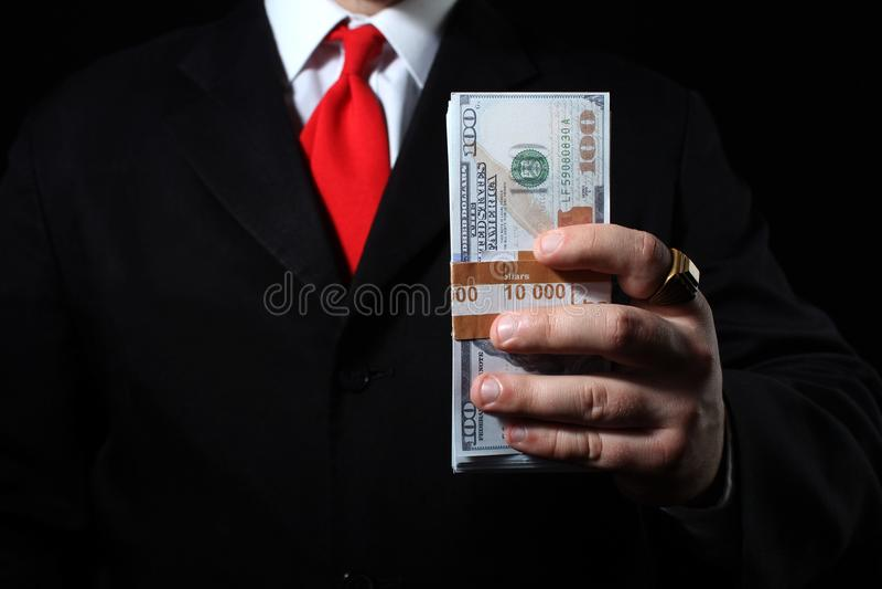 Paquete rico de la tenencia del hombre de negocios de dinero imagenes de archivo