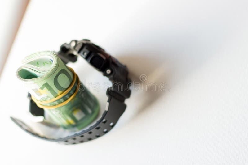Paquete rodado de cientos notas del euro dentro de la correa bloqueada del reloj moderno aislada en el fondo blanco fotos de archivo