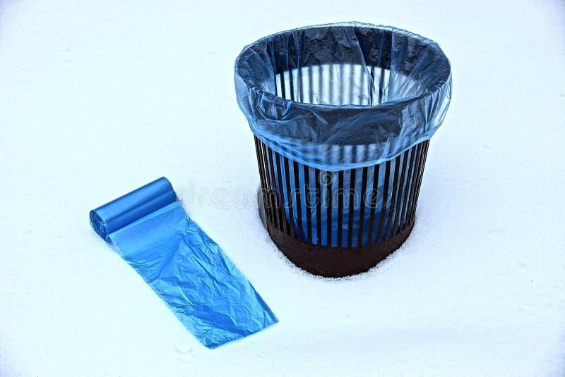 Paquetes azules y un cubo de la basura en la nieve blanca foto de archivo libre de regalías
