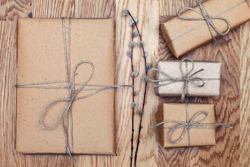 Paquetes de papel envueltos y atados en el documento de Kraft sobre una tabla de madera Estilo de la vendimia Visión superior fotos de archivo