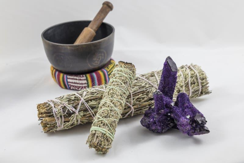Paquetes de sabio con un cuenco púrpura hermoso del cristal y del canto de cuarzo fotos de archivo libres de regalías
