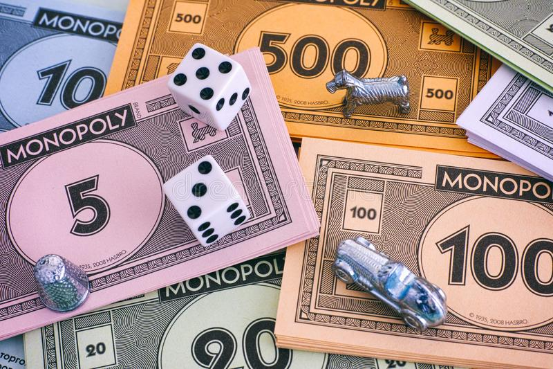 Paquetes del dinero del monopolio con los símbolos y los dados imagenes de archivo