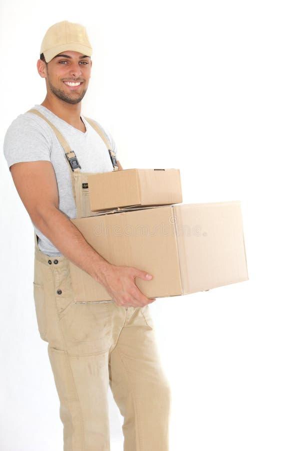 Paquetes que llevan jovenes del hombre de entrega imagen de archivo