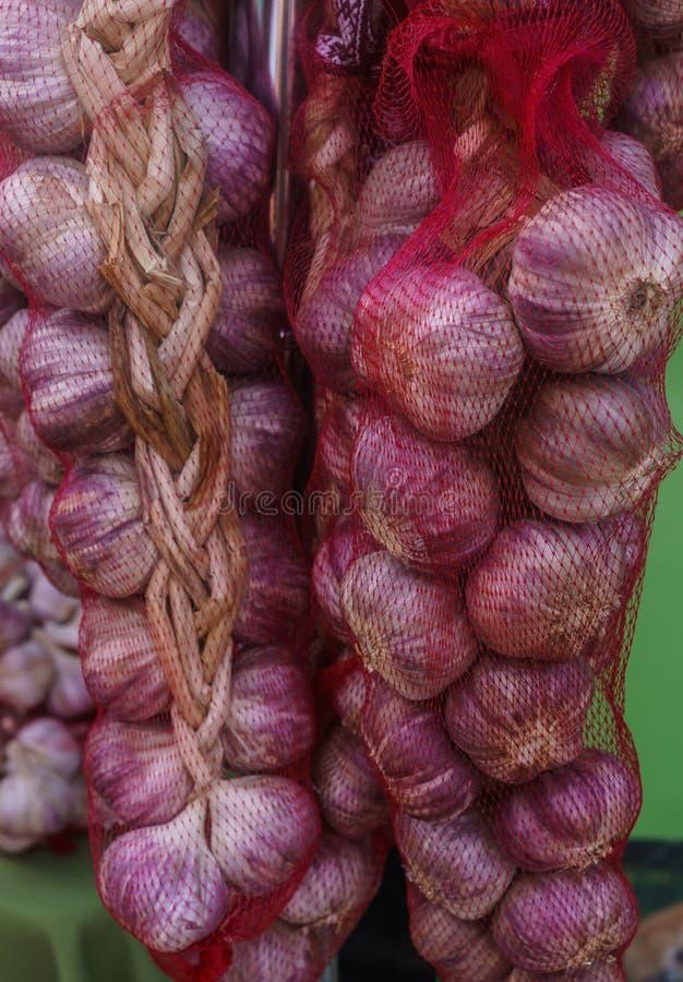 Paquets d'ail frais dans une grille décorative, suspendus sur un poteau photos libres de droits