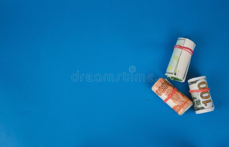 paquets d'argent tordu de diff?rentes devises sur un fond bleu photographie stock libre de droits