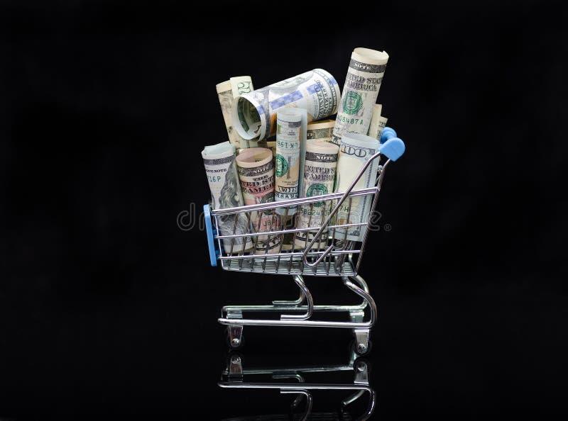 Paquets de petits pains de dollars US pleins et de caddie de factures sur le fond noir avec la réflexion photographie stock libre de droits