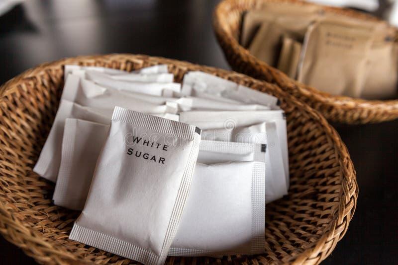 Paquets de sucre blanc dans le plateau en bambou images libres de droits