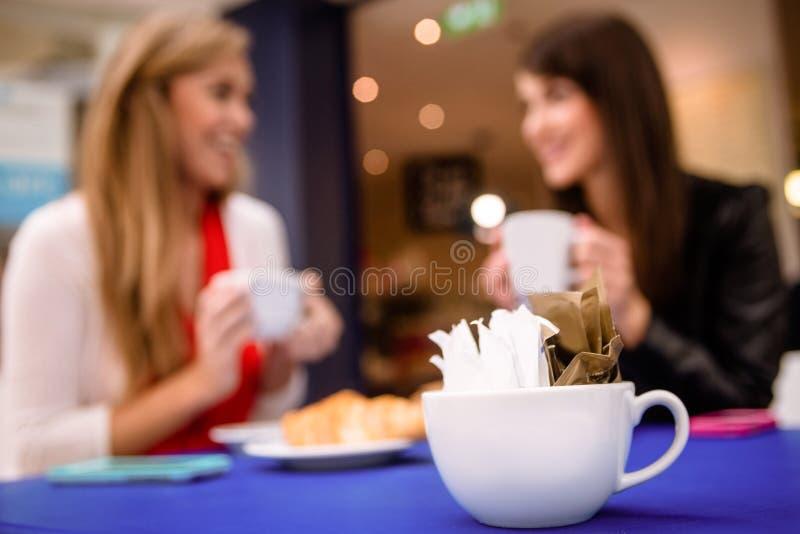 Paquets de sucre dans une tasse sur la table photographie stock libre de droits