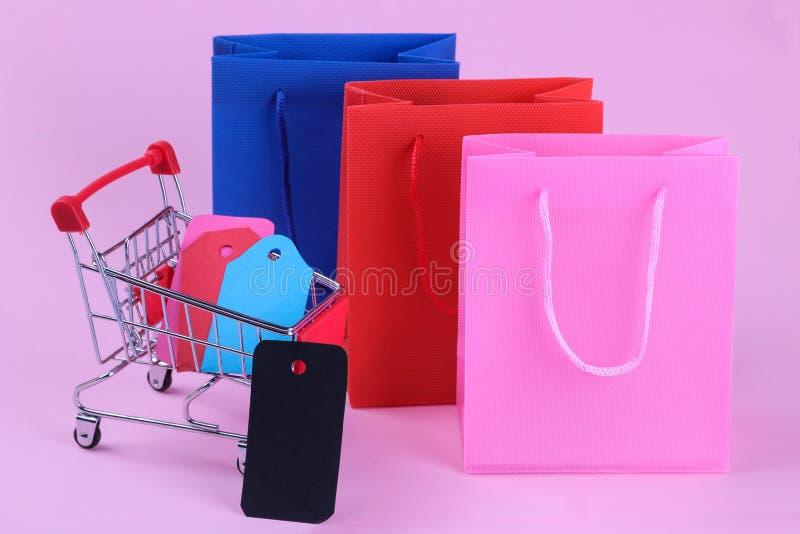 paquets pour des achats et un chariot à achats à l'intérieur avec différentes étiquettes et prix à payer sur un fond rose lumineu photographie stock libre de droits