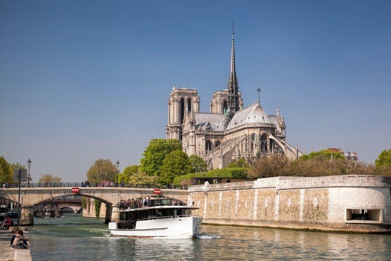 París, catedral de Notre Dame con el barco en el Sena, Francia imagen de archivo libre de regalías
