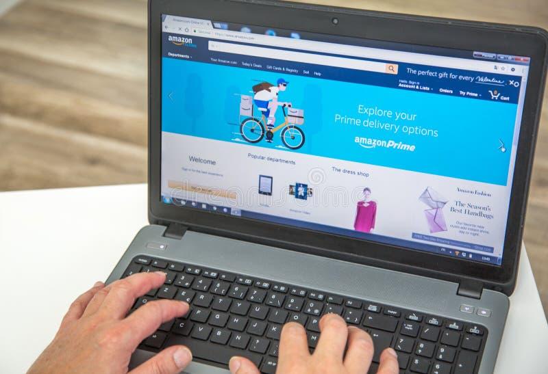 París, Francia - 27 de enero de 2017: Hombre que usa un ordenador portátil para conectar con el homepage de la prima del Amazonas foto de archivo