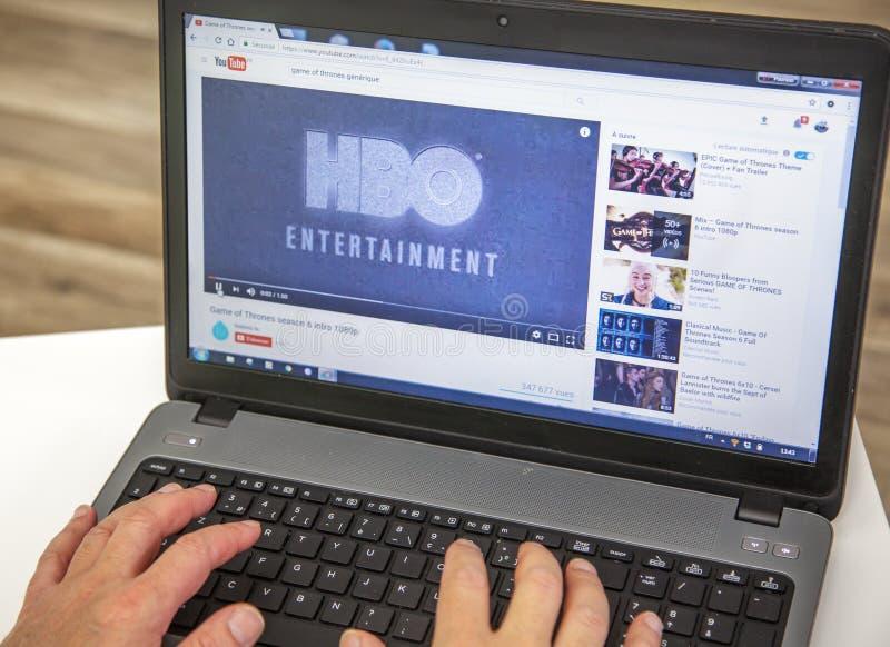 París, Francia - 27 de enero de 2017: Hombre que usa un ordenador portátil y YouTube para mirar un remolque de HBO de la serie te fotos de archivo libres de regalías