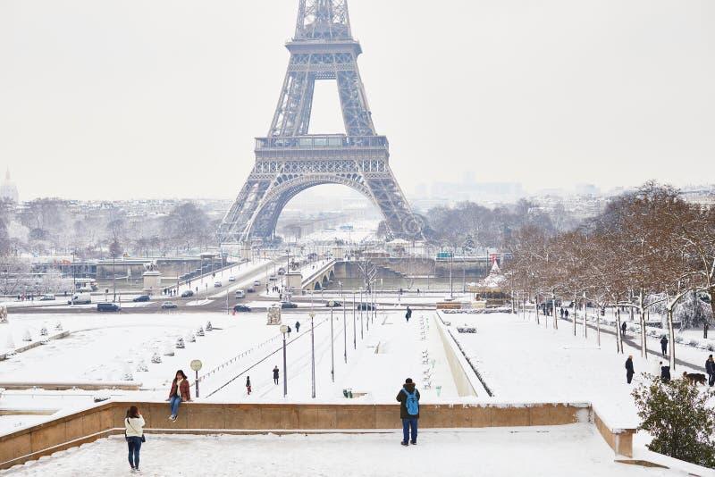 PARÍS, FRANCIA - 7 DE FEBRERO DE 2018: turistas que disfrutan de la visión escénica a la torre Eiffel en un día con nevadas fuert imagen de archivo