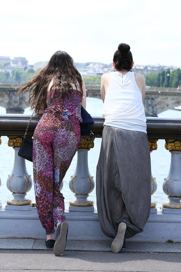 París, Francia - 14 de julio de 2014: dos turistas de las chicas jóvenes, admirando el paisaje parisiense sobre el puente alexand imagen de archivo