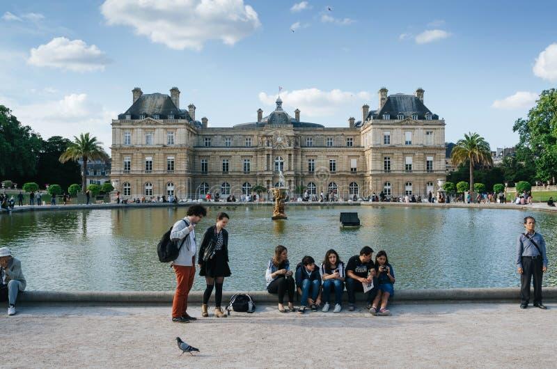 PARÍS, FRANCIA - 26 DE JUNIO DE 2016: La gente se relaja y cuelga hacia fuera en parque del pucturesque cerca de la fuente delant foto de archivo libre de regalías