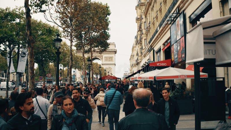 PARÍS, FRANCIA - 7 DE OCTUBRE DE 2017 Camine a lo largo de la acera apretada de la calle de Champs-Elysees hacia Arc de Triomphe  imagen de archivo libre de regalías