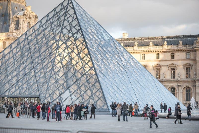 PARÍS, FRANCIA, EL 25 DE NOVIEMBRE DE 2012: Museo del Louvre exterior con la gente turística en París, Francia imagen de archivo libre de regalías