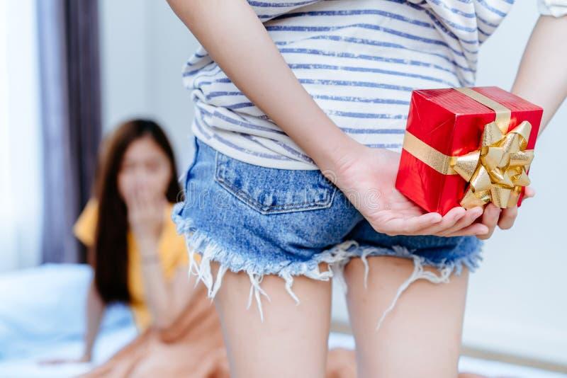 Paröverraskning för lesbisk kvinna LGBT med gåvaasken att ge sig till flickvännen arkivfoton