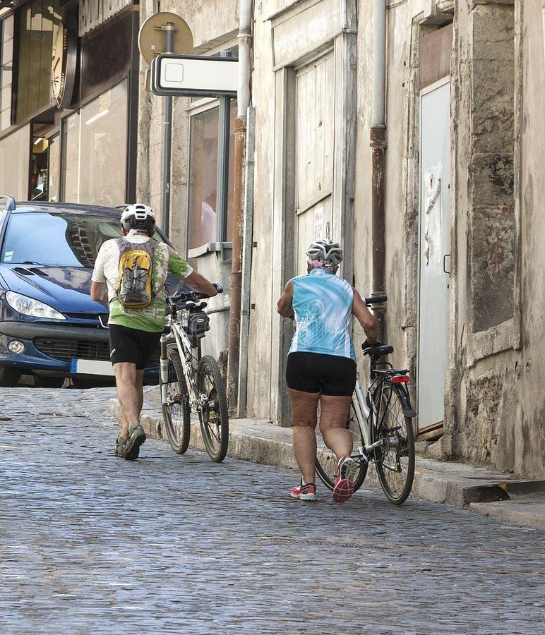 Par av äldre cyklister på gatan av den gamla staden royaltyfria foton