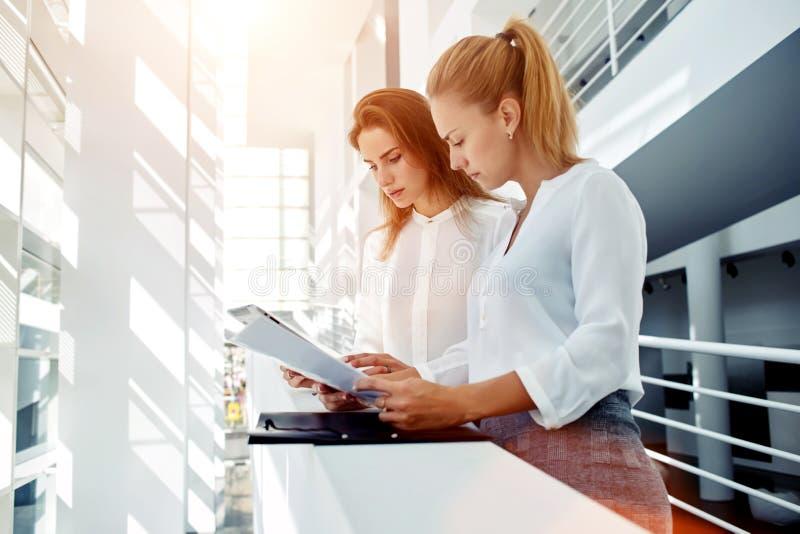 Par av affärskvinnor som läser pappers- dokument och använder handlagblocket för, förbereder sig till möte av partners royaltyfri foto