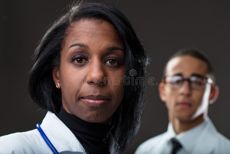 Par av afro--amerikan doktorer på mörk bakgrund arkivfoto