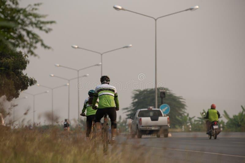 par av asiatiska cyklister, en man och kvinnaridningen på vägen i guld- royaltyfria bilder