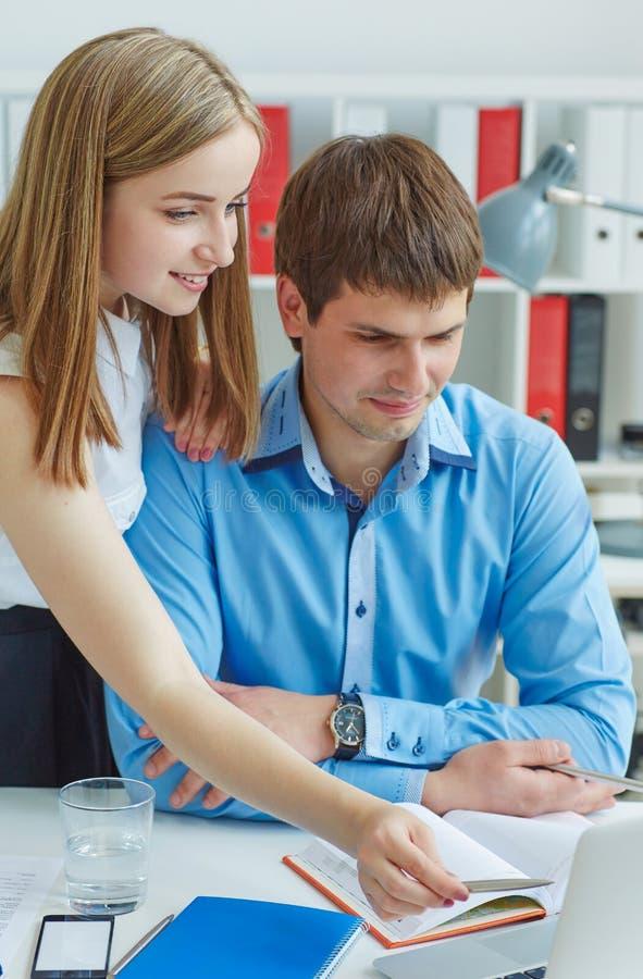 Par av barn som ler kollegor som ser bärbar datorskärmen i processen av diskussioner på utkastet fotografering för bildbyråer