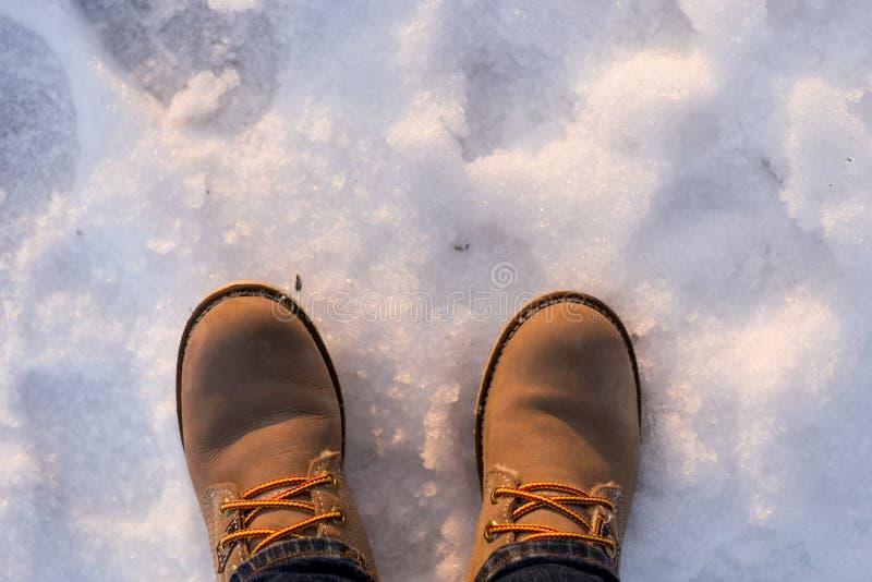 Par av beigea kängor för kvinna på solig dag för insnöad vinter Begrepp av choise, beslut, ensamhet, ensamhet, tystnad, fördjupni arkivfoto