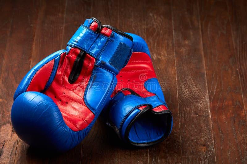 Par av blåa och röda boxninghandskar som ligger på den bruna trätabellen arkivfoto
