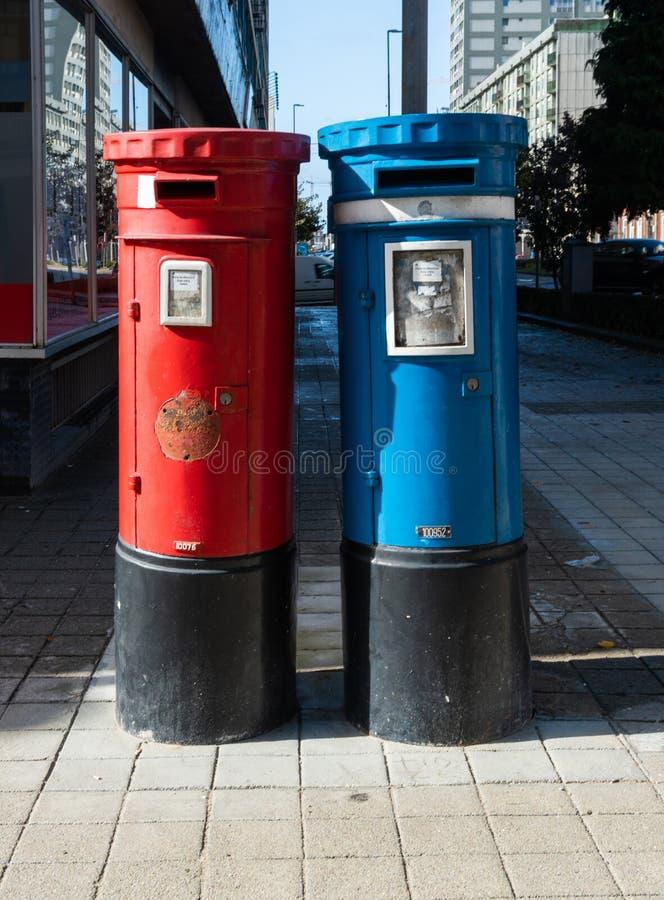 Par av brevlådan som är blåa och som är röda på gatan fotografering för bildbyråer