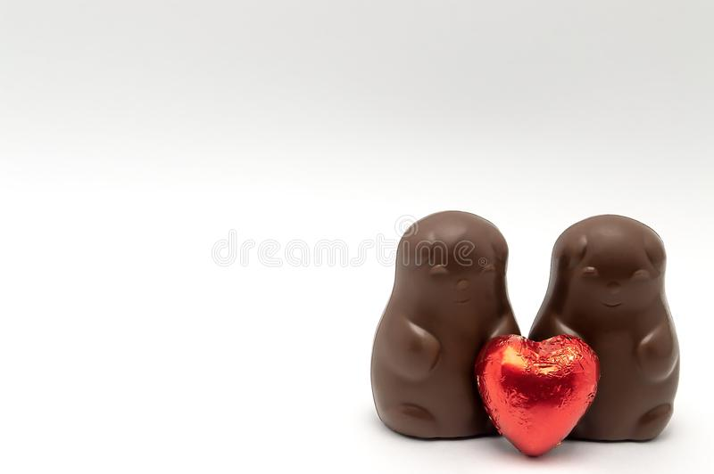 Par av chokladbjörnar med röd hjärta på en vit bakgrund älskar valentins dagisolaten arkivfoto