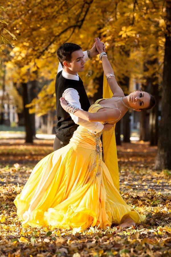 Par av dansare som dansar i träna Mannen med dräkten, kvinna i den gula långa klänningmitt av slotten parkerar i höst Torrt stupa royaltyfri fotografi