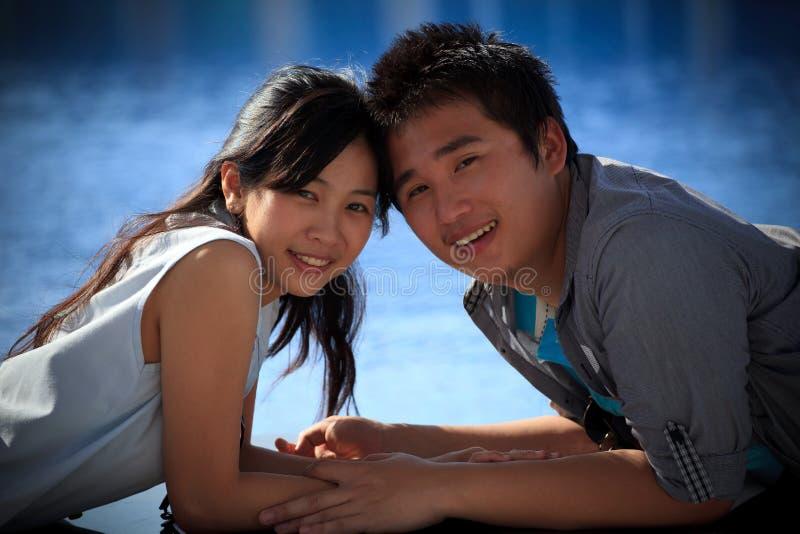 Par av den asiatiska mannen och kvinnan på vattenpölen royaltyfri bild