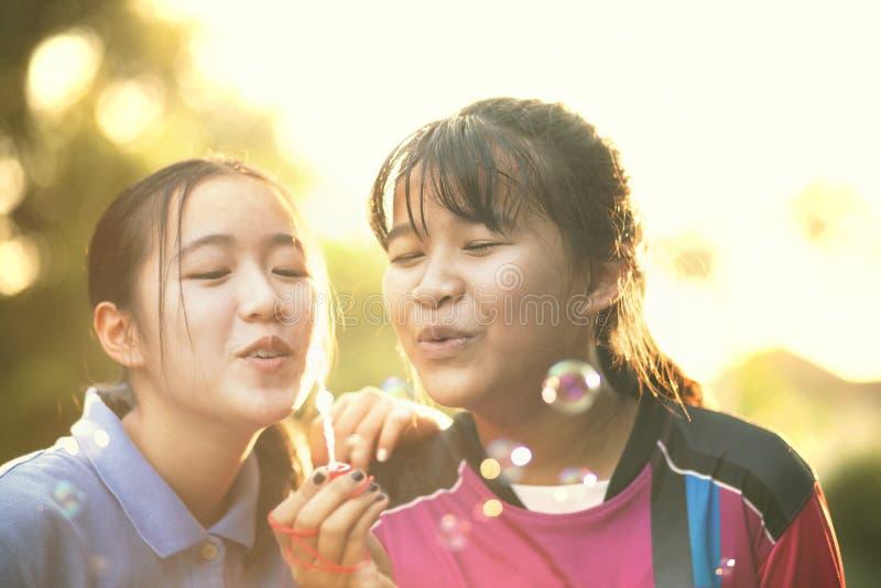 Par av den asiatiska tonåringen som kopplar av med soppabubblan mot härligt solljus royaltyfri fotografi