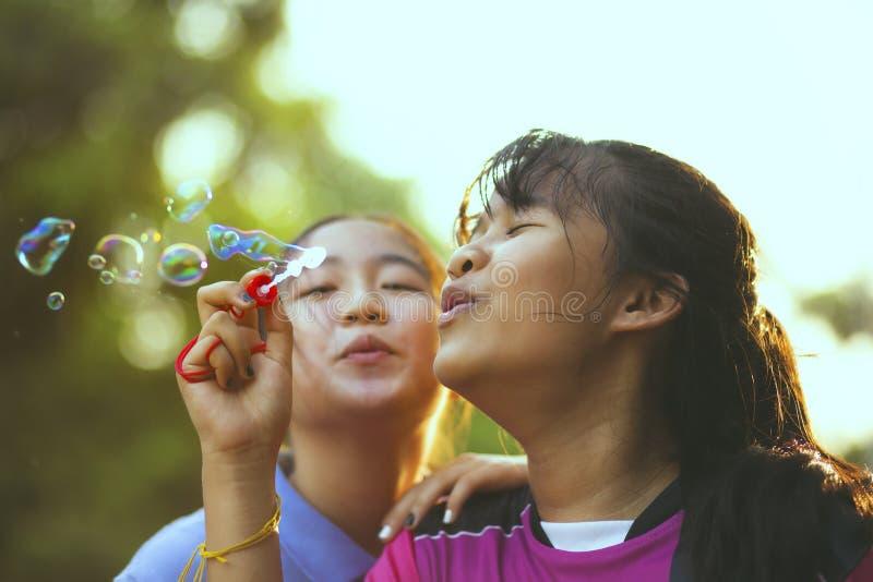 Par av den asiatiska tonåringen som kopplar av med soppabubblan mot härligt solljus royaltyfria foton