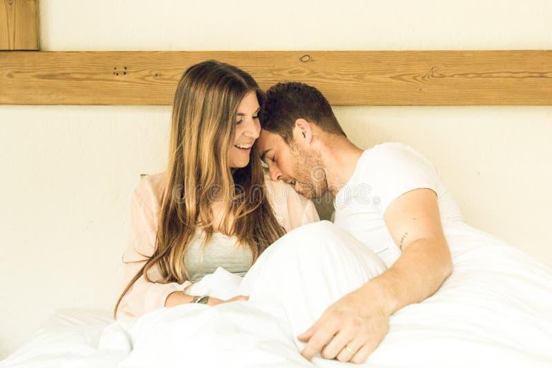 Par av den lyckliga grabben och flickan i säng som ler och Flickan och grabben kopplar ihop visningaffektion i säng arkivfoton