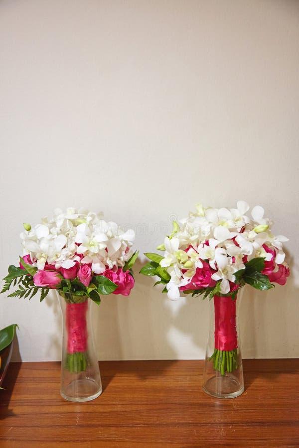 Par av den röda buketten för för ros som och vit blomma dekorerar med det röda rosa bandet på den glass vasen royaltyfria bilder