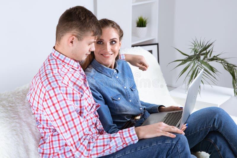 Par av den unga mannen och kvinnan direktanslutet i internet som hemma sitter på en soffa royaltyfria bilder